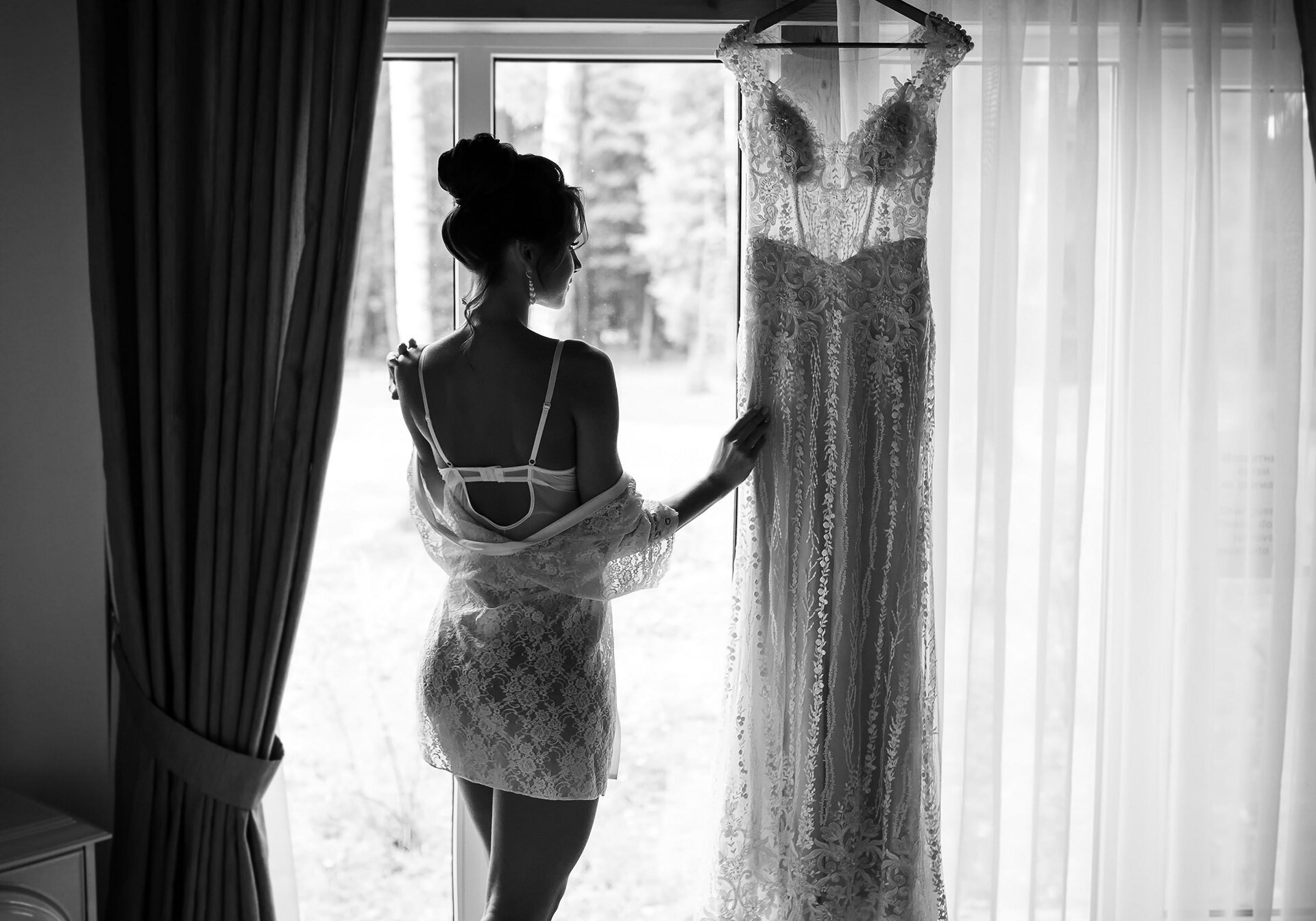 Bride morning preparation. Beautiful sexy bride in white wedding negligee and veil near the window. Tender morning of the bride