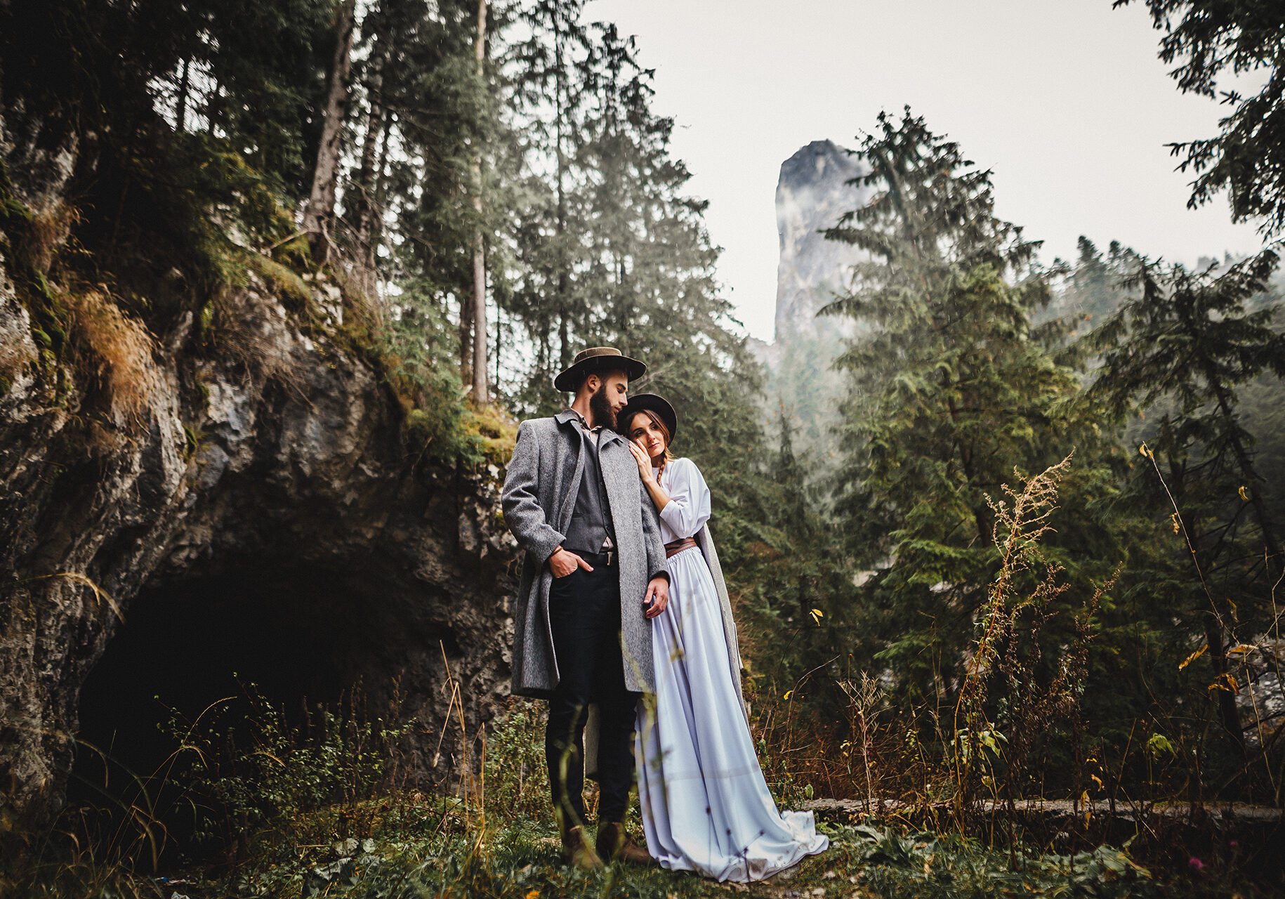Beautiful loving couple going for a walk in a misty forest and cave